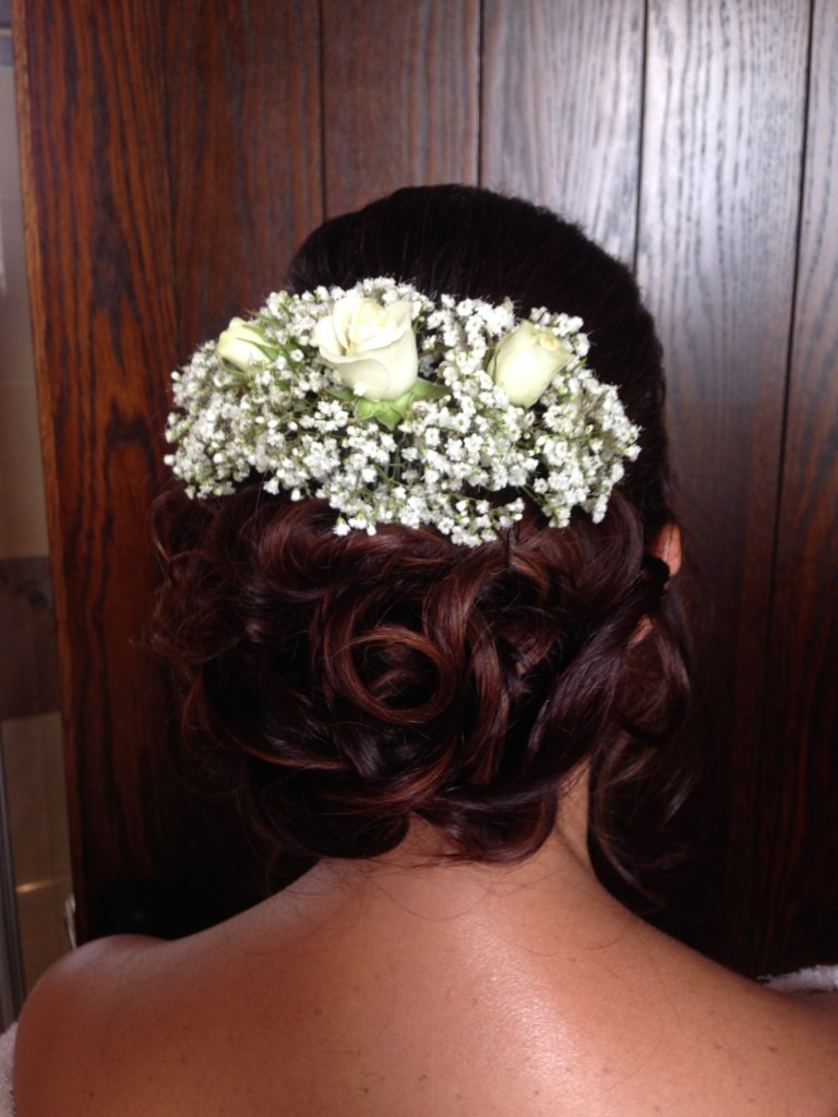 Curled bridal bun hairstyle with natural flowers